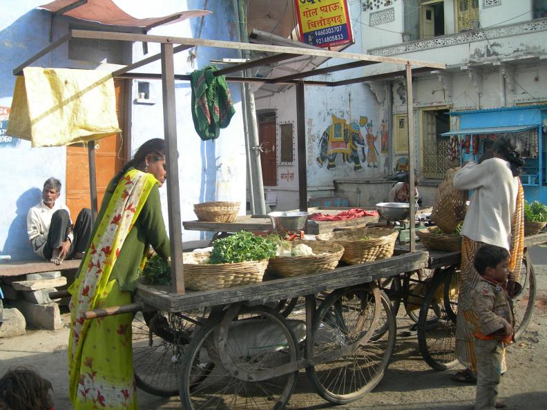 Obchod se zeleninou -- V postranní uličce si rozložil svůj pojízdný krámek místní zemědělec. Zatímco si zákazníci vybírají zboží, on odpočívá na stoličce opodál. Až výběr dokončí, přijde vyinkasovat platbu. Pokud si nic nevyberou, nestojí mu za vstávání.