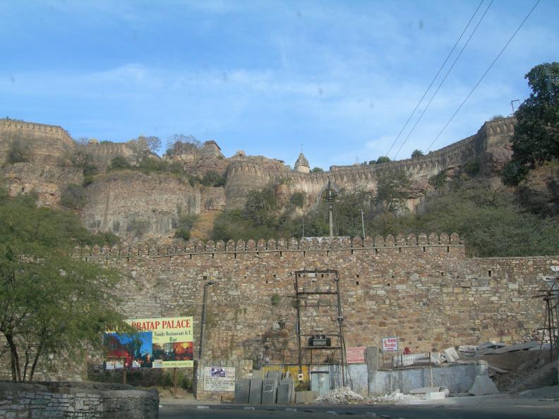 Pod pevností -- Na úpatí kopce narážíme na první hradby pevnosti. Silnička strmými serpentinami vystoupá podle hradeb asi sto výškových metrů na náhorní plošinu na kopci nad městem.