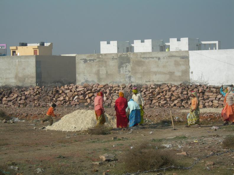 Stavební práce 1 -- Stavba v naší kolonii se přesouvá i do oblasti kde dříve bylo jen rumiště a křoví. Až bude stavba hotová, bude náš dům stát uprostřed satelitního městečka. Tady se zatím budují příjezdové silnice před budoucími domy. Pracovnice roznášejí štěrk na cestu v lavorech na hlavách. Pracují tu jen ženy a některé mají s sebou i své děti. Při práci se nezastavují, ale nepřetržitě si nahlas mezi sebou povídají.