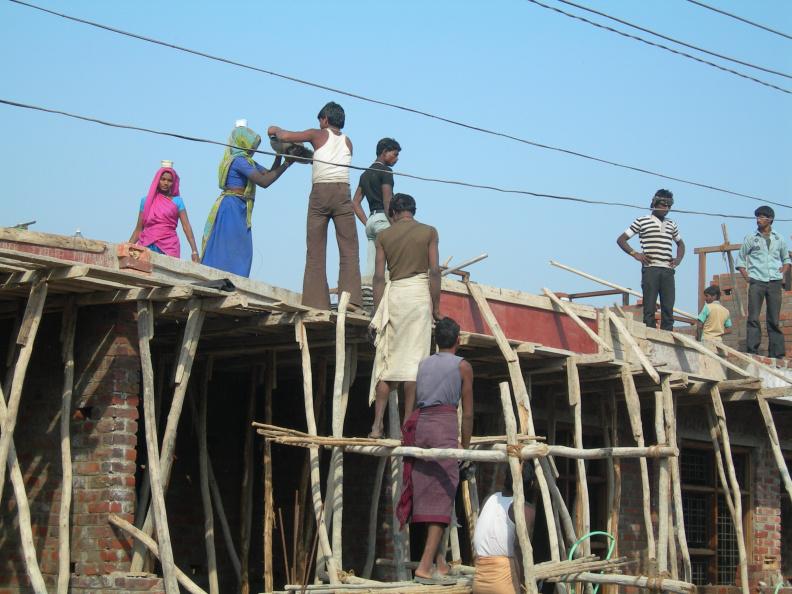 Stavební práce 3 -- I na střeše roznášejí namíchanou maltu v lavorech ženy na hlavách. Někteří muži podávají lavory nahoru, jiní přihlížejí a odpočívají.